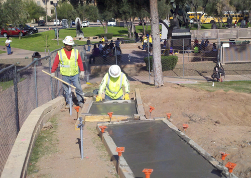 Workers set the foundation for the monoliths that comprise the Bill of Rights monument.